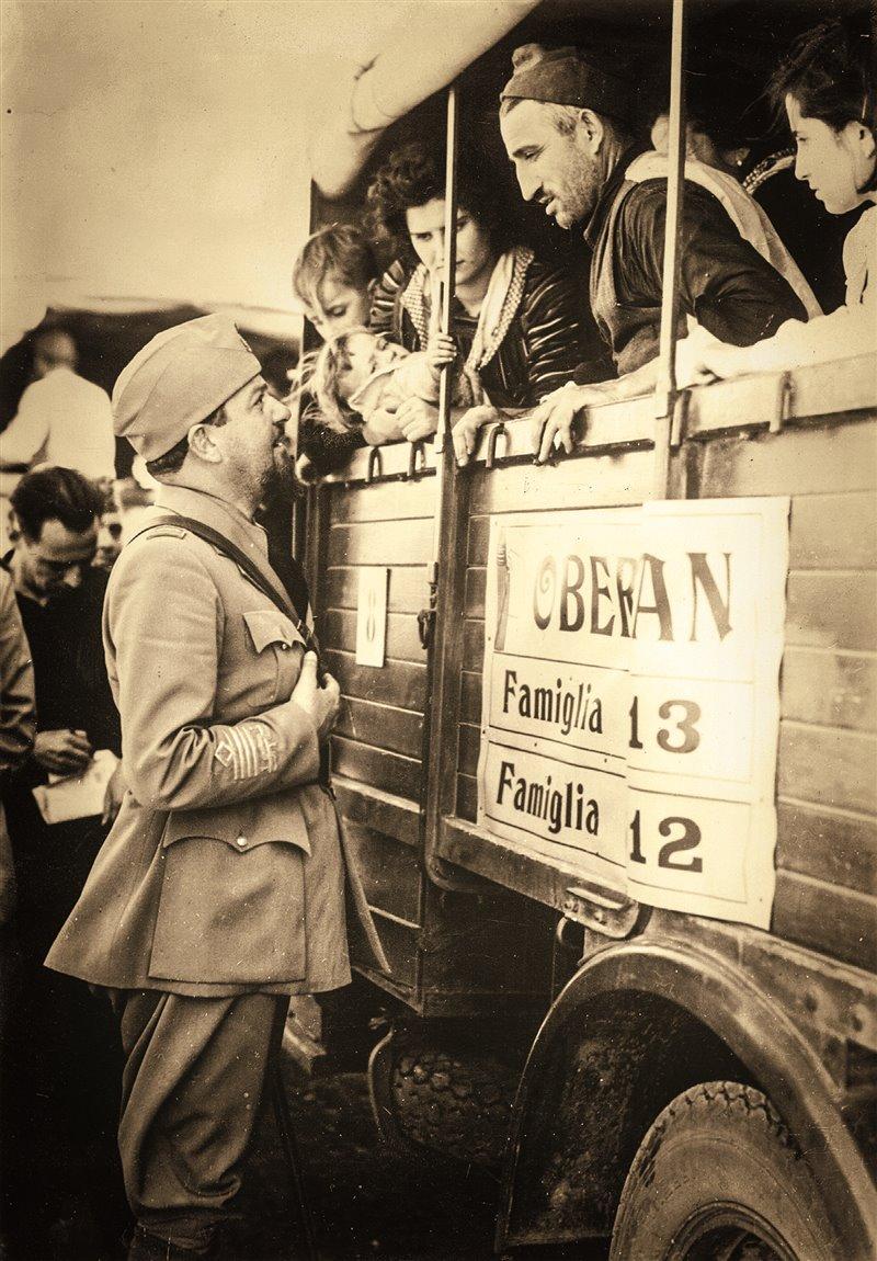 Questo scatto del 1939 ritrae i futuri coloni mentre vengono condotti in camion agli insediamenti in Libia