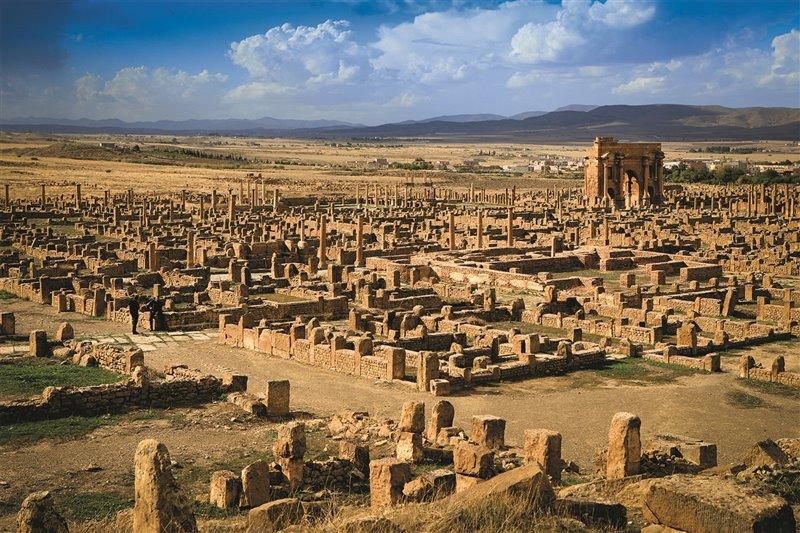 Vista generale delle rovine della città romana di Timgad, in Algeria. Sullo sfondo è visibile l'arco monumentale eretto in omaggio all'imperatore Traiano