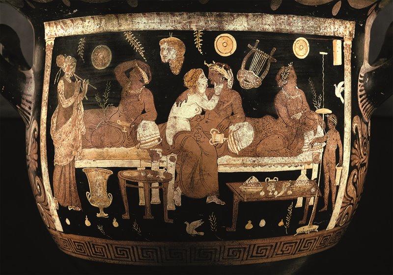 Un'etèra accarezza il suo amante a un banchetto. Si possono notare le tavole basse su cui si disponevano gli alimenti e il cratere in cui si mescevano vino e acqua. Museo Archeologico Nazionale di Napoli