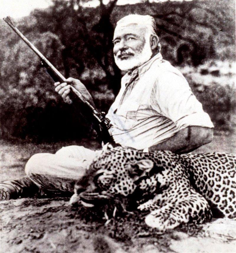 Lo scrittore e giornalista Ernest Hemingway accanto a un leopardo ucciso durante una battuta di caccia in Uganda nel gennaio 1954