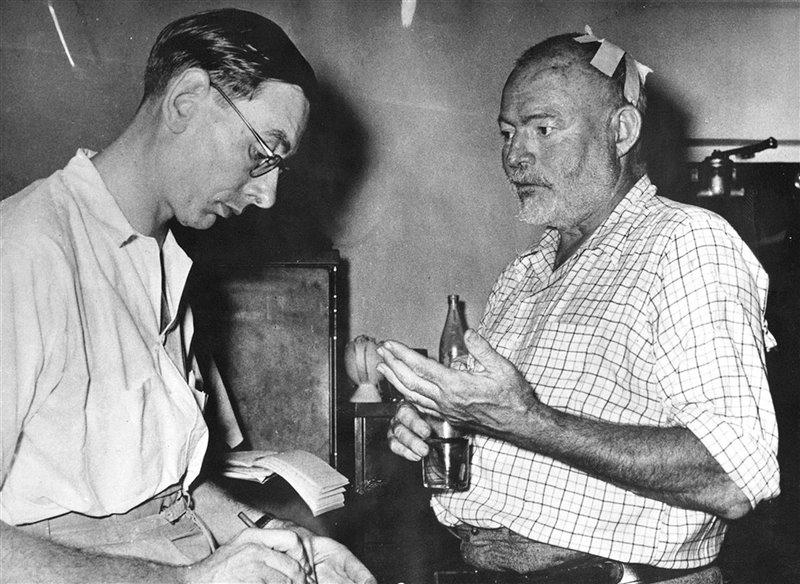 Lo scrittore intervistato da un giornalista a Entebbe, Uganda, il 25 gennaio 1954, pochi giorni dopo il doppio incidente aereo. Una benda copre la ferita alla testa